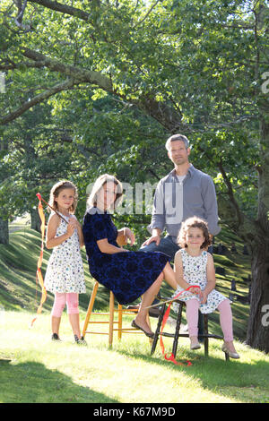 a happy, smiling family poses with red streamers outside in the sun - Stock Photo
