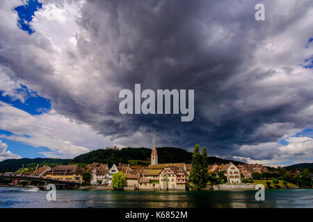 A panoramic view on the small town across the river Rhine, dark thunderstorm clouds above - Stock Photo