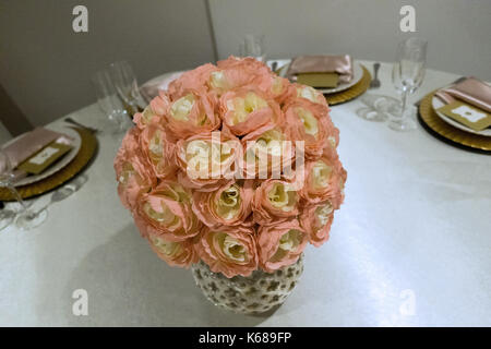 A pink vase of flowers in the middle of a table set for invited guests. - Stock Photo