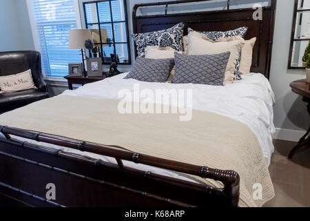 A large bed with sham pillows, nightstands and an armchair in a cozy bedroom. - Stock Photo