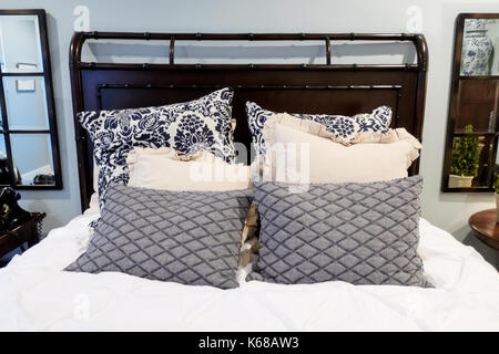 A large bed with sham pillows in a cozy master bedroom. - Stock Photo