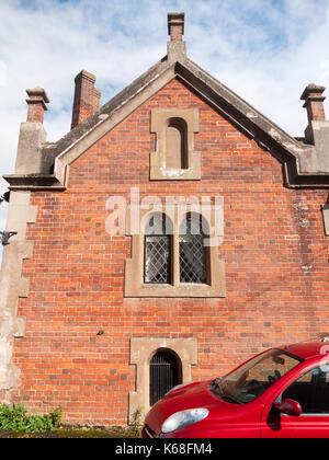 close up of church hall side brick windows above red car; England; UK - Stock Photo