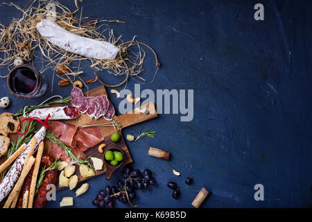 Charcuterie snacks on wood background. Salami and cheese served with red wine. Top view, copy space. - Stock Photo