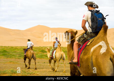Khongor, Mongolia - July 20, 2007: Rear view of foreign tourists riding double humped bactrian camels at the Khongor - Stock Photo