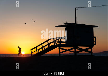 Silhouettes of a sportive runner working out on the sand and the iconic lifeguard tower with flying birds at sunset - Stock Photo
