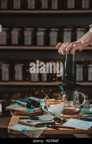 Preparing coffee in AeroPress with a dynamic coffee splash and still life with maps and traveller essentials -- - Stock Photo