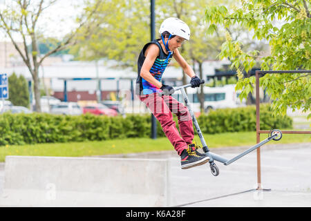 Saguenay, Canada - June 3, 2017: Downtown city summer park in Quebec with young teenager boy skating, performing - Stock Photo