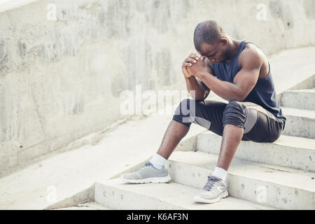 Young man runner resting after workout session on sunny morning. male fitness model sitting on street along pond - Stock Photo
