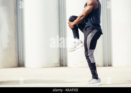 Image of muscular young man working out against sky. African man looking away with stretching his leg. Shirtless - Stock Photo