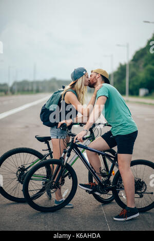 Romantic sports couple kissing against blurred background with bicycles. Pink Kinesio tape glued on the girl's hand. - Stock Photo