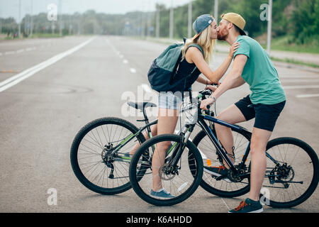 Beautiful young couple in love walking with bicycles, kissing and hugging. Stand near the bikes. The concept of - Stock Photo