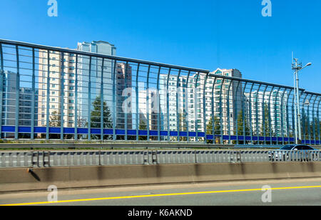 High barriers separate traffic lanes and shelter high rise apartments on Jeju Island in South Korea - Stock Photo