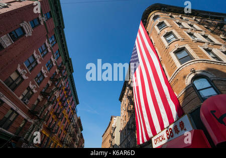 Giant American flag hanging on a tenement  building in Chinatown, New York City, in Lower Manhattan - Stock Photo