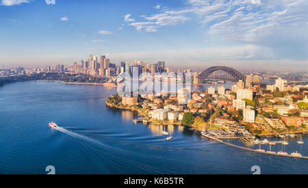 Kirribilli yacht club, headland and marina in front of Sydney city CBD, harbour bridge and landmarks around waters - Stock Photo