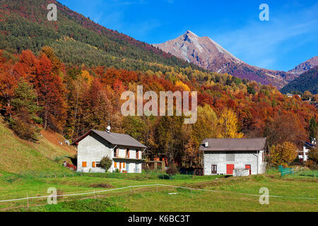 Rural houses on green lawn as colorful autumnal trees and mountains on background under blue sky in Switzerland. - Stock Photo
