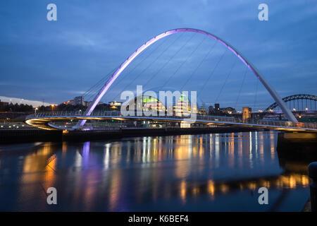 The Newcaste-Upon-Tyne/Gateshead quayside at dusk, showing the Sage, Milennium and Tyne bridges - Stock Photo
