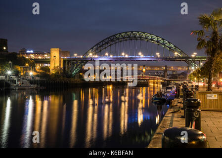 The Newcaste-Upon-Tyne/Gateshead quayside at night, showing the Tyne bridge and reflections in the River Tyne - Stock Photo