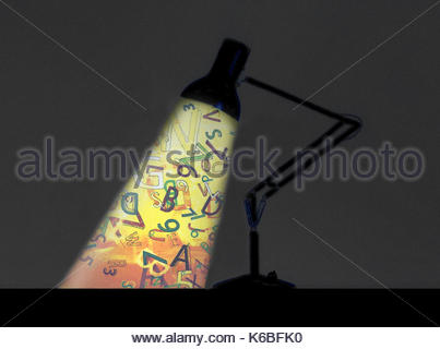 Letters and numbers in spotlight from desk lamp - Stock Photo