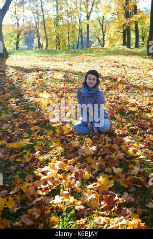 happy young teen girl in autumn scenery throwing leaves - Stock Photo