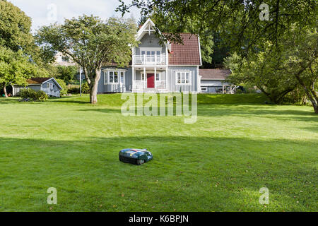 Robotic lawnmower on grass lawn in beautiful garden in front of idyllic wooden house  Model Release: No.  Property - Stock Photo