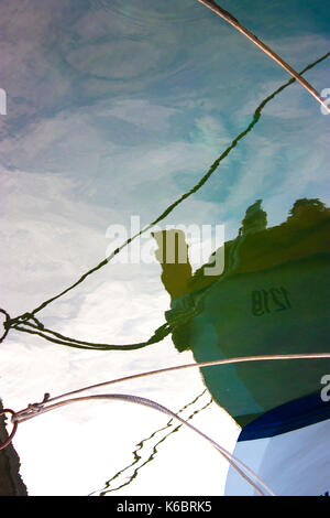 Blurry reflection of a boat fasten to the shore in the sea upside down; - Stock Photo