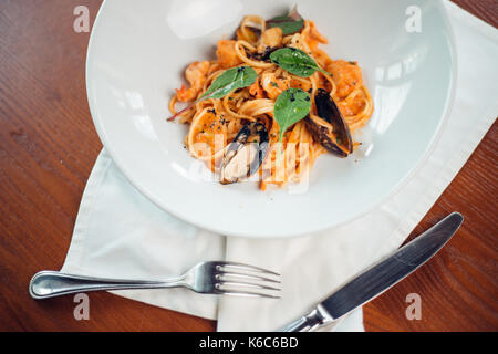 Seafood Pasta with mussels and basil in white plate on wooden table. - Stock Photo