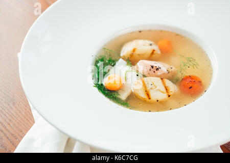 Chicken soup with noodles and vegetables in bowl over rustic wooden background - Stock Photo