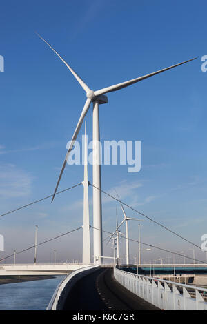 Wind turbines and an asphalted two way bicycle path near canal Hartel in Rotterdam - Stock Photo