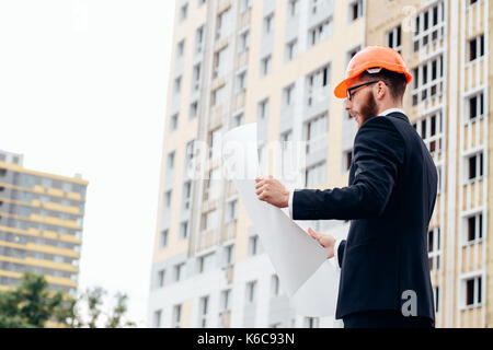 Portrait of an architect builder studying layout plan of the rooms, serious civil engineer working with documents - Stock Photo