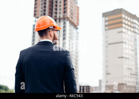 Back of business engineer wearing a white helmet is pointing his hand to show the building construction, a progressed - Stock Photo