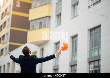 Engineer man in helmet and jacket controlling outdoor construction site - Stock Photo