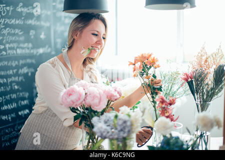 Smiling lovely young woman florist arranging plants in flower shop - Stock Photo