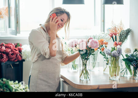 Portrait of young female florist talking on phone and making notes at flower shop. - Stock Photo