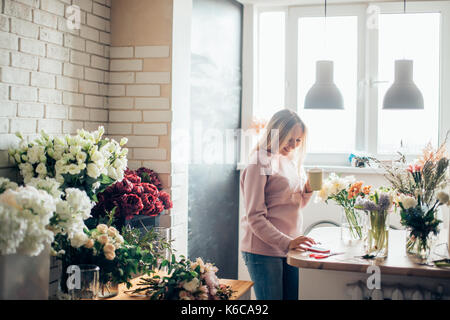 Florist at work. A woman in the process of making a summer bouquet of peonies, holds in her hand a cup of coffee. - Stock Photo