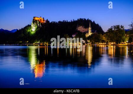Illuminated Bled Castle, Blejski grad, located on a rocky mountain, seen across Lake Bled, Blejsko jezero at night - Stock Photo