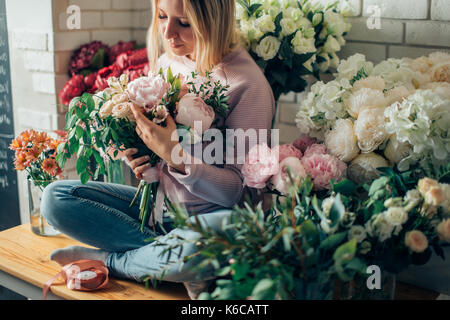 Florist shop in daylight. Woman holding beautiful bouquet of flowers. Florist with her work. Stylized tender photo - Stock Photo