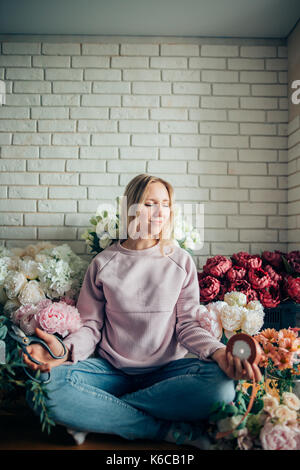Cute lovely young woman florist sitting in lotus position in flower shop. - Stock Photo