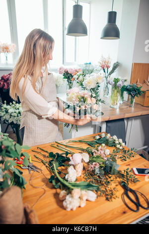 Small business. Male florist unfocused in flower shop. Floral design studio, making decorations and arrangements. - Stock Photo