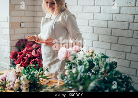 woman florist taking pictures of flowers with mobile phone - Stock Photo