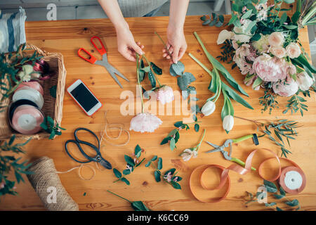 hands of florist against desktop with working tools and ribbons on wooden background - Stock Photo