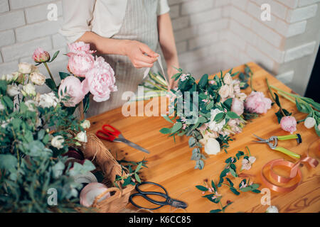 Woman making bouquet of narcissus. Top view of florist hands arranging and decorating flowers. - Stock Photo