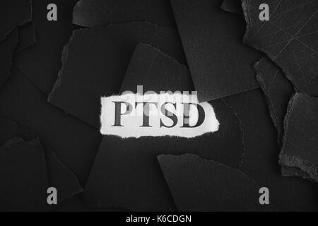 Post Traumatic Stress Disorder. Torn pieces of black paper and words Post Traumatic Stress Disorder. Concept Image. Black and White. Closeup.