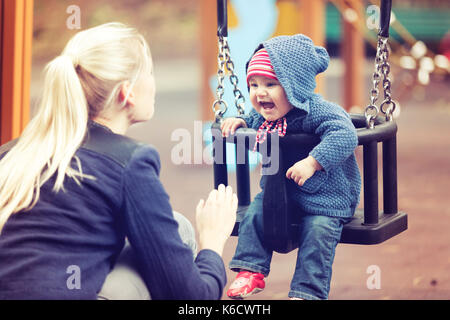 mother with her child having fun on playground swing on autumn day - Stock Photo