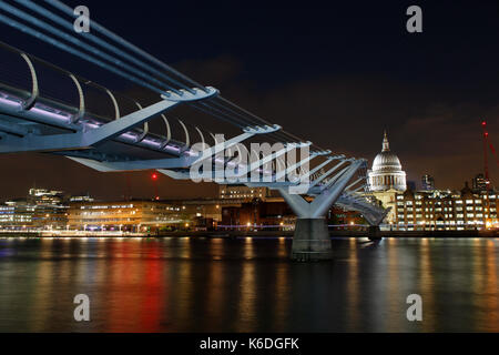 The Millennium Bridge at night with St Paul's Cathedral in the background. - Stock Photo