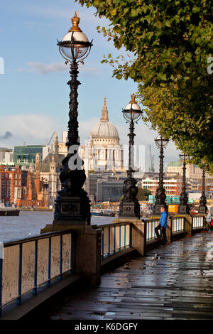 London South Bank with St Paul's Cathedral framed by ornate lamp posts,looking east from Waterloo bridge - Stock Photo