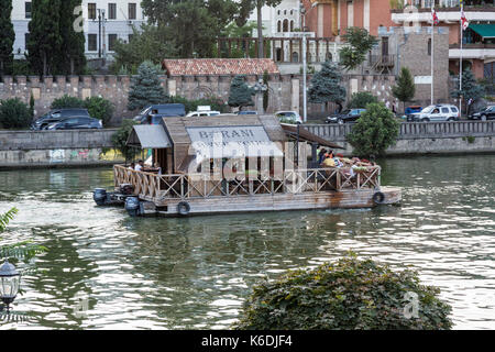 Tourist boat cruising on the Kura River in the centre of Tbilisi in Georgia. - Stock Photo