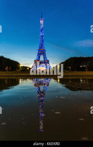 The illuminated Eiffel Tower is reflected in the water Champ de Mars Paris France Europe - Stock Photo