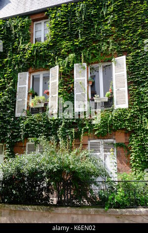 An urban garden in a house in Rue Lepic in Montmartre, Paris with beautiful shutters, flowers and green ivy on the - Stock Photo
