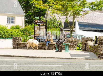 Male with goat on lead sat next to the statue of the great Kerry sporting legend John Egan - Stock Photo
