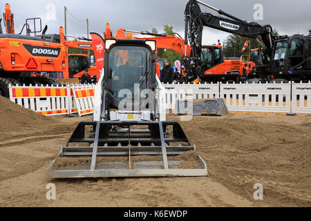HYVINKAA, FINLAND - SEPTEMBER 8, 2017: Operator levels ground with Bobcat T450 Compact Track Loader and landplane - Stock Photo